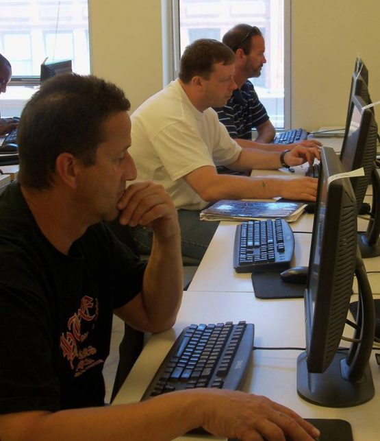 Three men using computers.