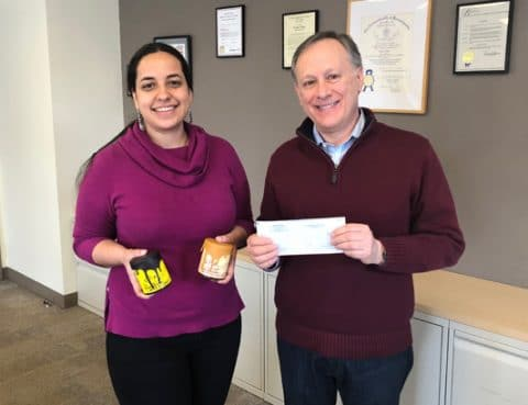 A man and a woman pose with a check