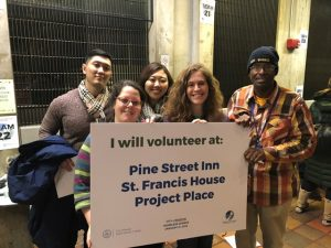 "Five people hold a sign that says ""I will volunteer at Pine Street Inn, St. Francis House, Project Place"""