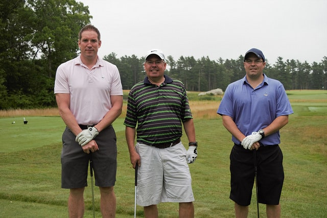 3 men, golf gloves on, standing side by side