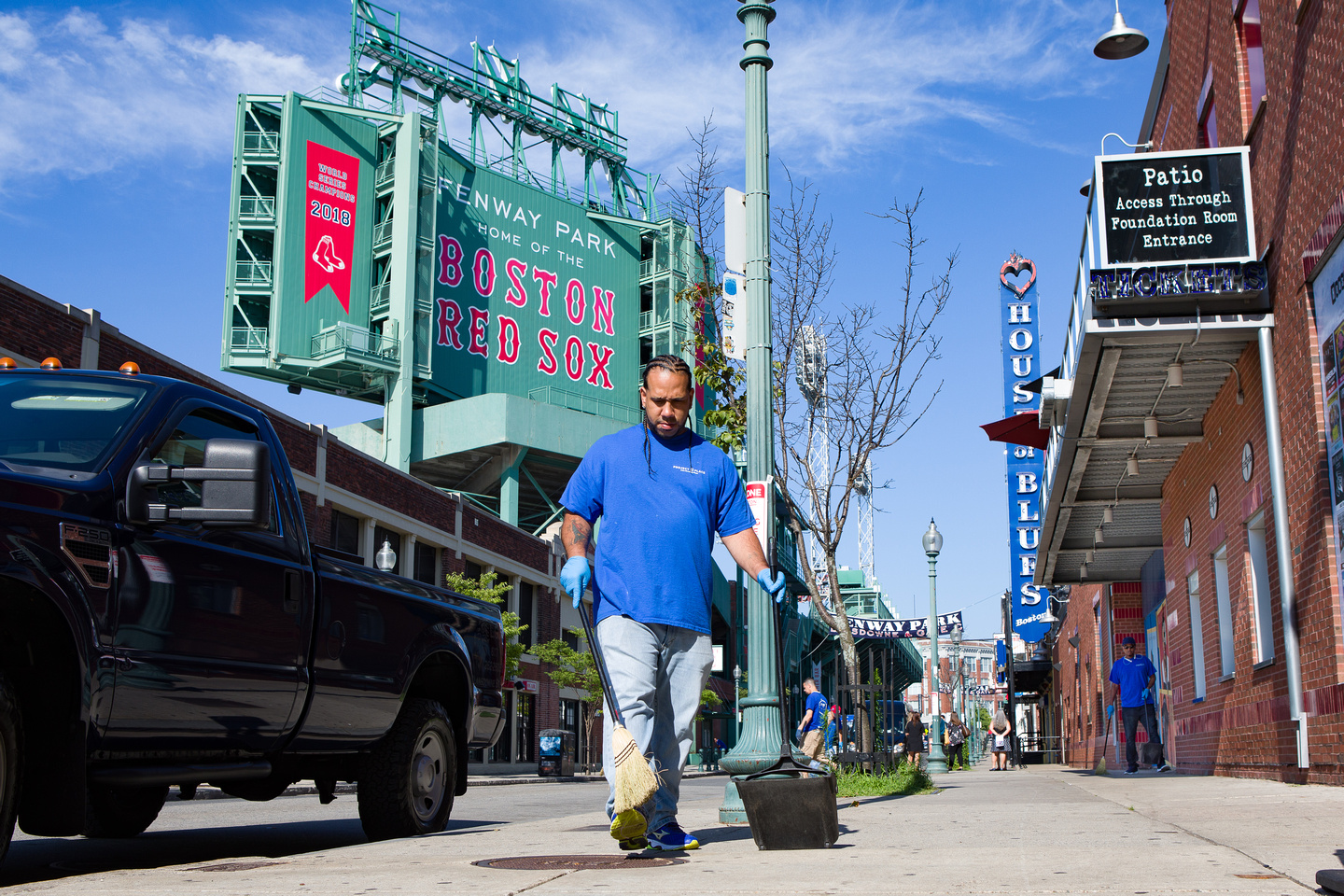 a client standing in front of the Fenway Park sign as he cleans the streets