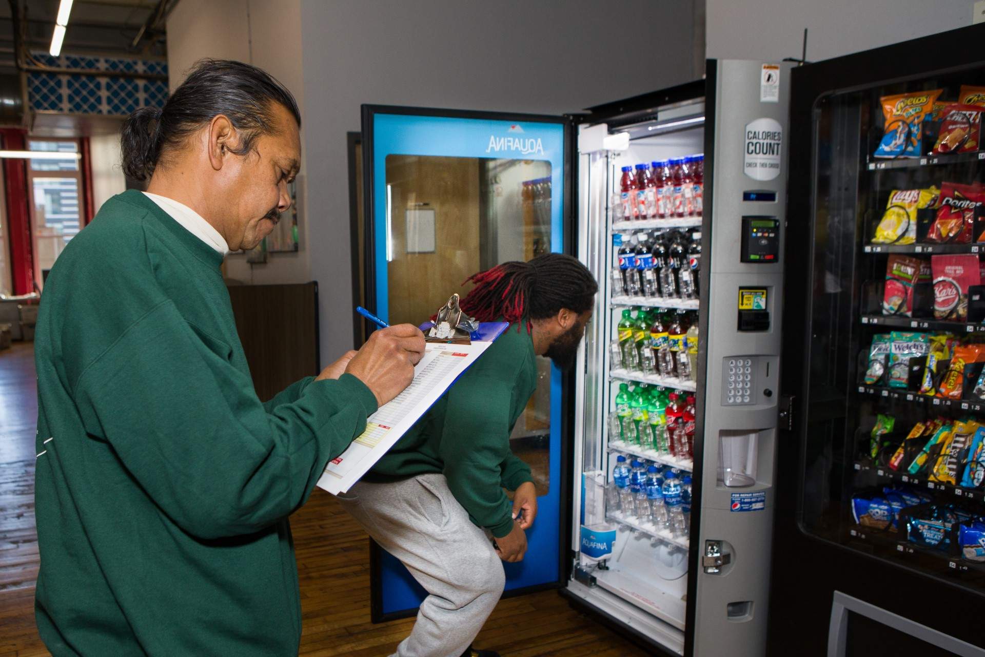 two clients in our LEAP social enterprise taking inventory and stocking a vending machine