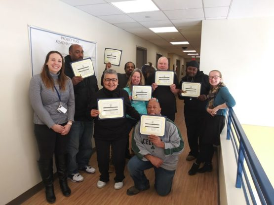 Newly graduated clients of our first stabilization program holding up their certificates