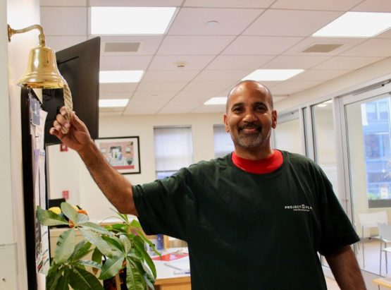 a client ringing a bell after finding employment